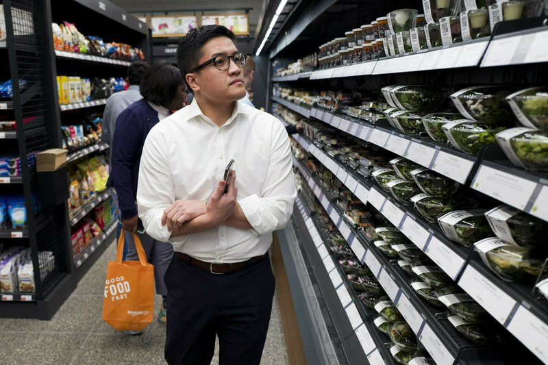 FILE - In this May 7, 2019, file photo a customer shops in a newly-opened Amazon Go store in New York. (AP Photo/Mark Lennihan, File)