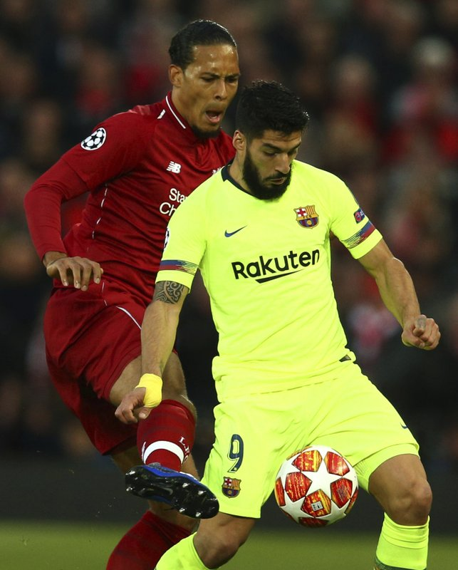 Liverpool's Virgil Van Dijk fights for the ball against Barcelona's Luis Suarez during the Champions League semifinal, second leg, soccer match between Liverpool and FC Barcelona at the Anfield stadium in Liverpool, England, Tuesday, May 7, 2019. (AP Photo/Dave Thompson)