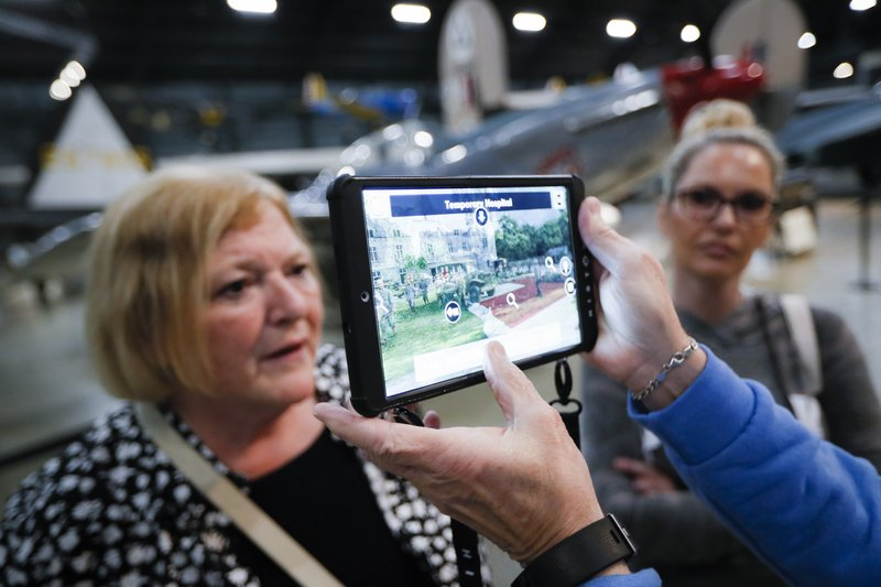 In this Friday, April 26, 2019 photo, Deane Sager, of Louisville, off camera, and his wife Cathy, left, use a Histopad tablet to view scenes from operations on the western front of World War II at the The National Museum of the U. (AP Photo/John Minchillo)