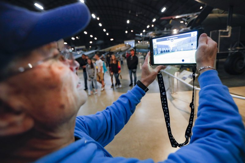 In this Friday, April 26, 2019 photo, Deane Sager, of Louisville, uses a Histopad tablet to view scenes from operations on the western front of World War II at the The National Museum of the U. (AP Photo/John Minchillo)