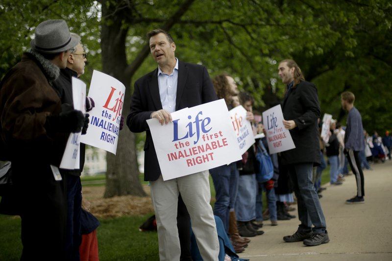 Former Kansas Secretary of State Kris Kobach, third from left, stands with about 100 anti-abortion demonstrators across the street from the Kansas Supreme Court building Thursday, May 9, 2019, in Topeka, Kan. (AP Photo/Charlie Riedel)