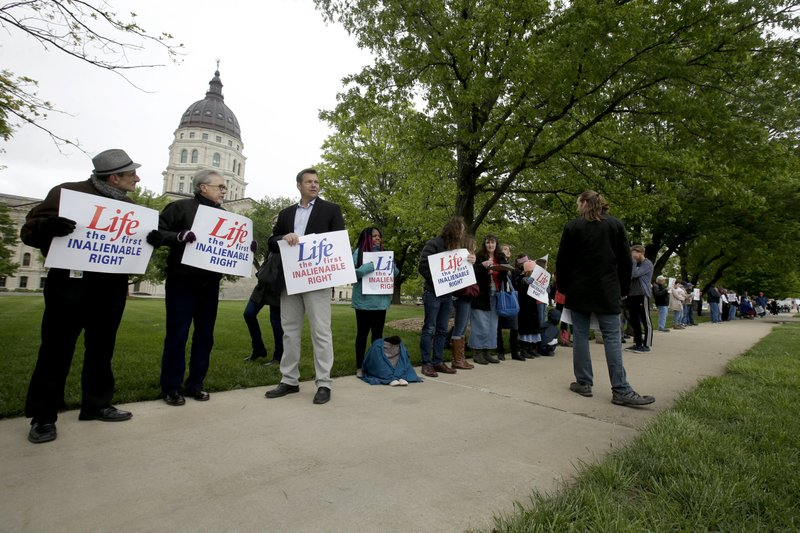 Former Kansas Secretary of State Kris Kobach, third from left, stands with about 100 pro-life supporters across the street from the Kansas Supreme Court building Thursday, May 9, 2019, in Topeka, Kan. (AP Photo/Charlie Riedel)