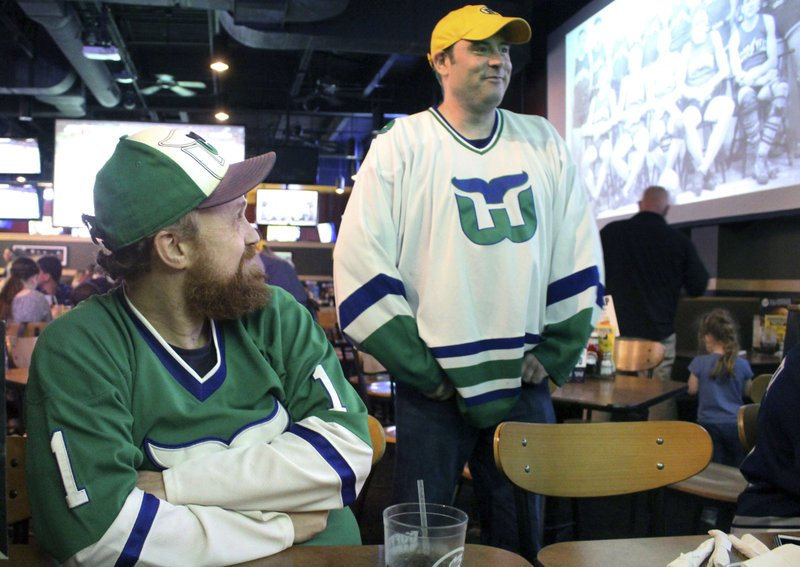 Scott St. Laurent, left, and Matthew Greene chat with other members of the Hartford Whalers Booster club, Thursday, May 9, 2019, at a restaurant in Manchester, Conn. (AP Photo/Pat Eaton-Robb)