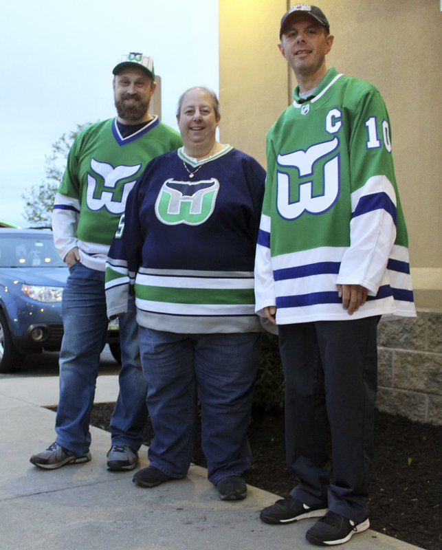 Hartford Whalers Booster Club members, from left, Scott St. Laurent, Joanne Coressa and Dan Narvesen pose outside a Manchester, Conn. (AP Photo/Pat Eaton-Robb)