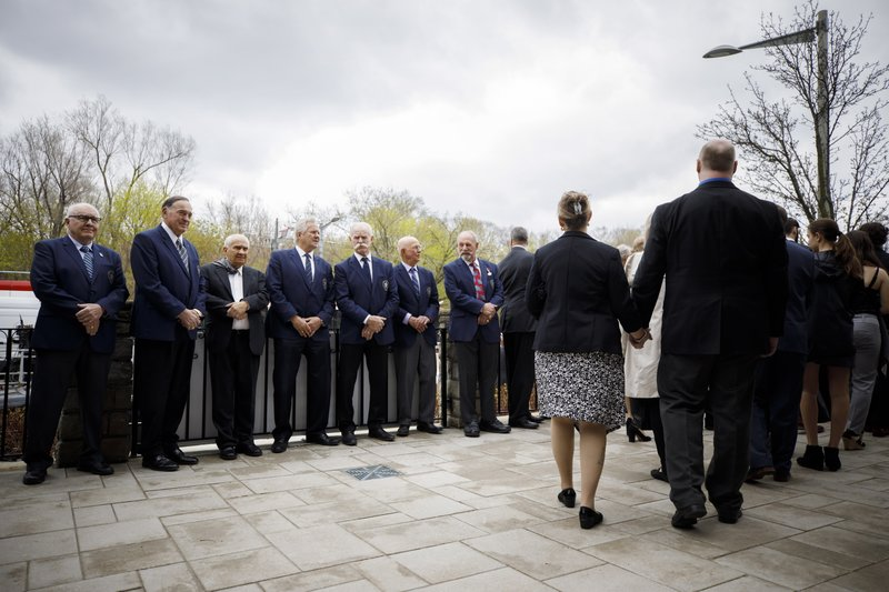 Toronto Maple Leafs' alumni, from left, Ron Ellis, Frank Mahovolich, Jim Gregory, Darryl Sittler, Lanny McDonald, Dick Duff, and Eddie Shack, stand in a row as mourners exit the church following the funeral Mass for NHL legend Leonard Patrick