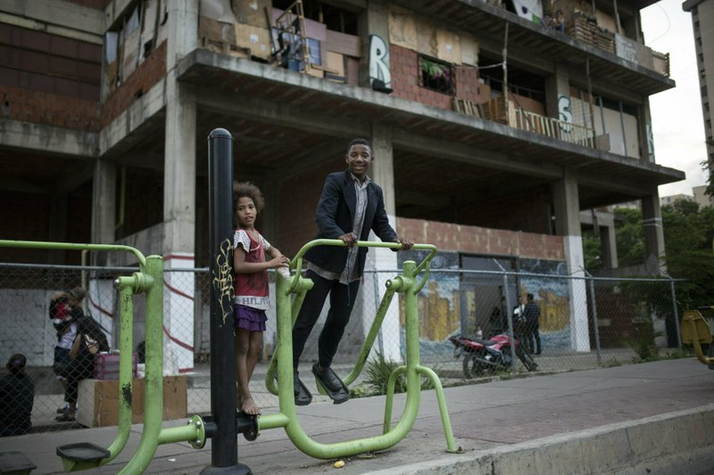 Children play outside a building occupied by squatters in Caracas, Venezuela, Thursday, May 9, 2019. In the fourth month of their standoff, Venezuela's President Nicolas Maduro and opposition leader Juan Guaidó are unable to deliver a knock-out blow as Venezuela spirals deeper into neglect, isolation and desperation. (AP Photo/Rodrigo Abd)