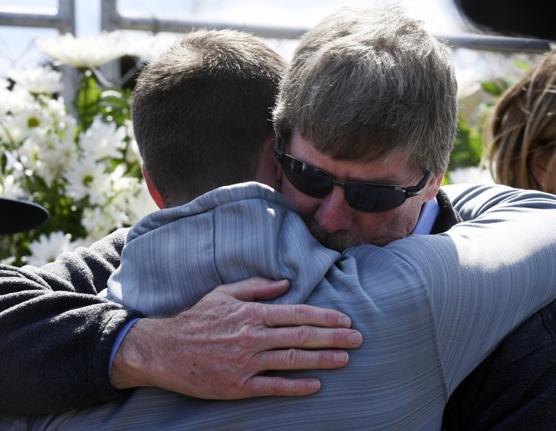 AB Specialty Silicones general manager Mac Penman, right, hugs people during a memorial, Friday morning, May 10, 2019, in Waukegan, Ill. (Joe Lewnard/Daily Herald via AP)