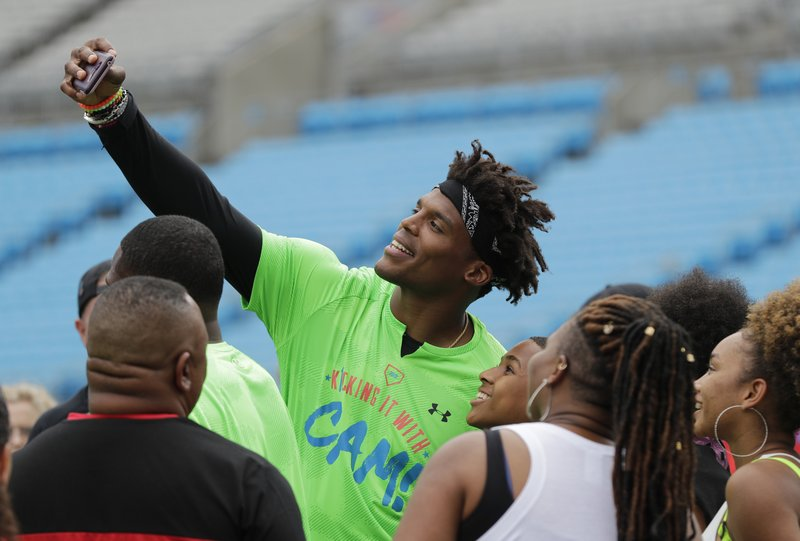 Carolina Panthers Cam Newton takes a selfie with fans during his charity kickball tournament in Charlotte, N. (AP Photo/Chuck Burton)