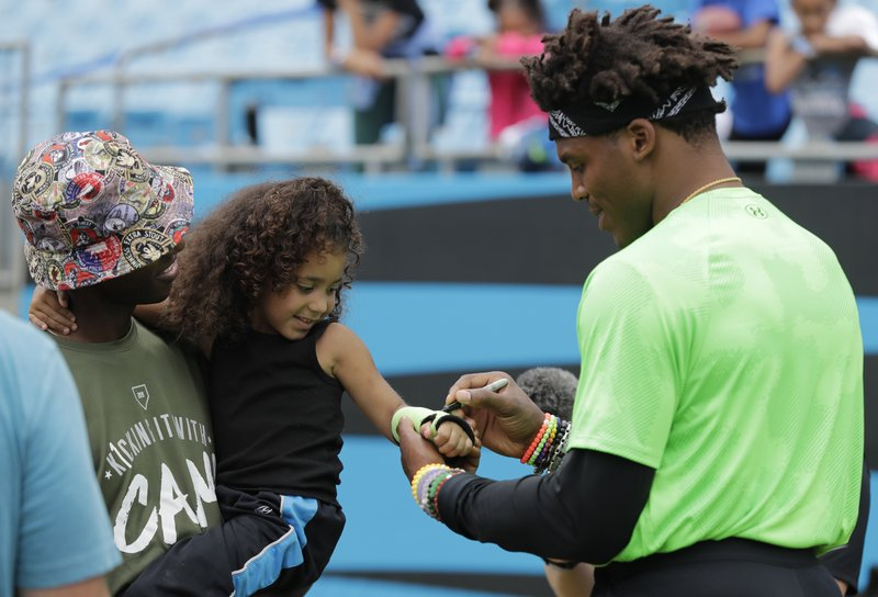 Carolina Panthers Cam Newton, right, signs an autograph during his charity kickball tournament in Charlotte, N. (AP Photo/Chuck Burton)