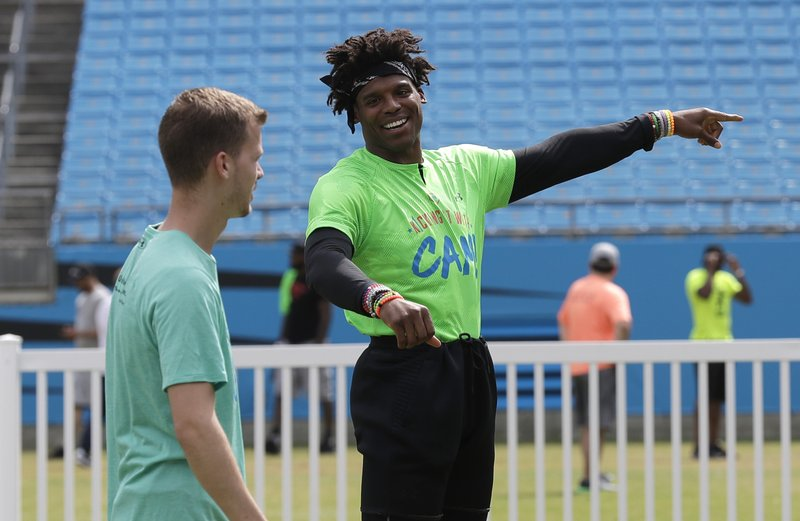 Carolina Panthers Cam Newton, right, jokes with a teammate during his charity kickball tournament in Charlotte, N. (AP Photo/Chuck Burton)