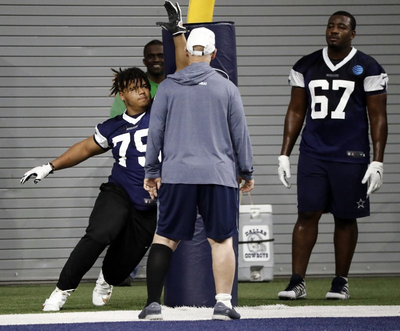 Dallas Cowboys defensive tackle Trysten Hill, left, runs through a drill as defensive coordinator and line coach Rod Marinelli, and defensive tackle Shakir Soto (67) watch during the NFL football team's minicamp in Frisco, Texas, Friday, May 10, 2019. (AP Photo/Tony Gutierrez)