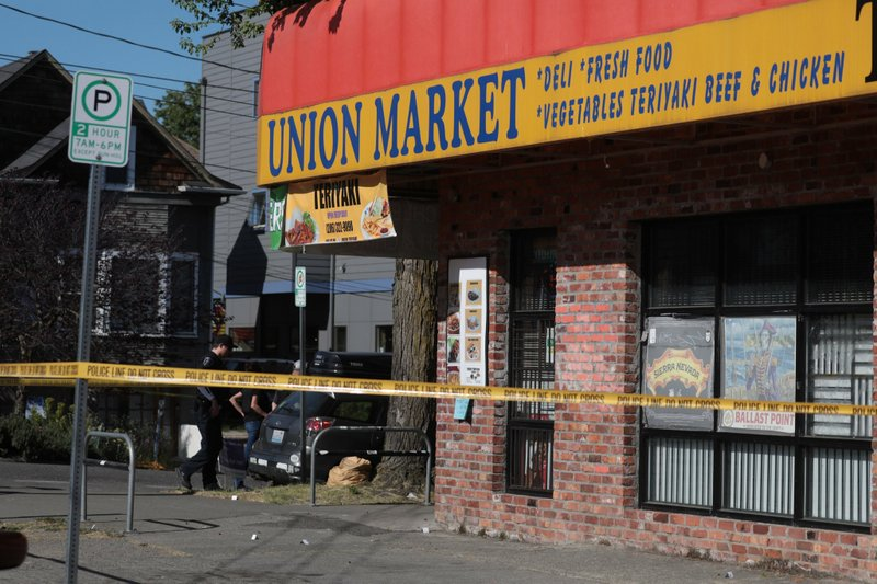 Police investigate a shooting Friday May 10, 2019, in Seattle. Chang Sunwoo, the owner of Union Teriyaki and Market near the site of the shooting, told the Seattle Times that he was inside his shop when he said he heard what sounded like 15 to 20 gun shots. (Bettina Hansen/The Seattle Times via AP)