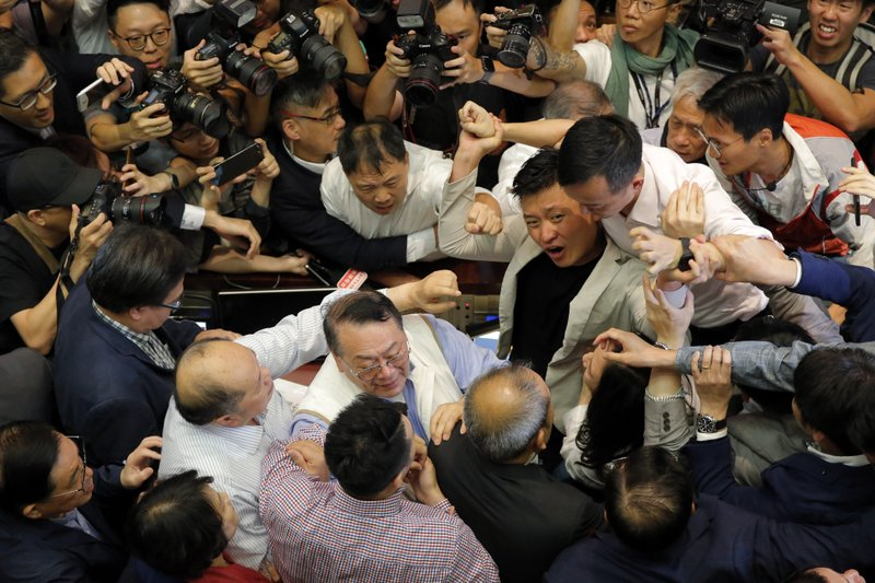 Pro-democracy and pro-Beijing lawmakers scuffle in the chamber at Legislative Council in Hong Kong, Saturday, May 11, 2019. (AP Photo/Kin Cheung)