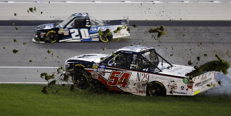 Natalie Decker (54) spins into the infield grass during the NASCAR Truck Series auto race at Kansas Speedway in Kansas City, Kan., Friday, May 10, 2019. Harrison Burton (20) gets by on the outside. (AP Photo/Colin E. Braley)