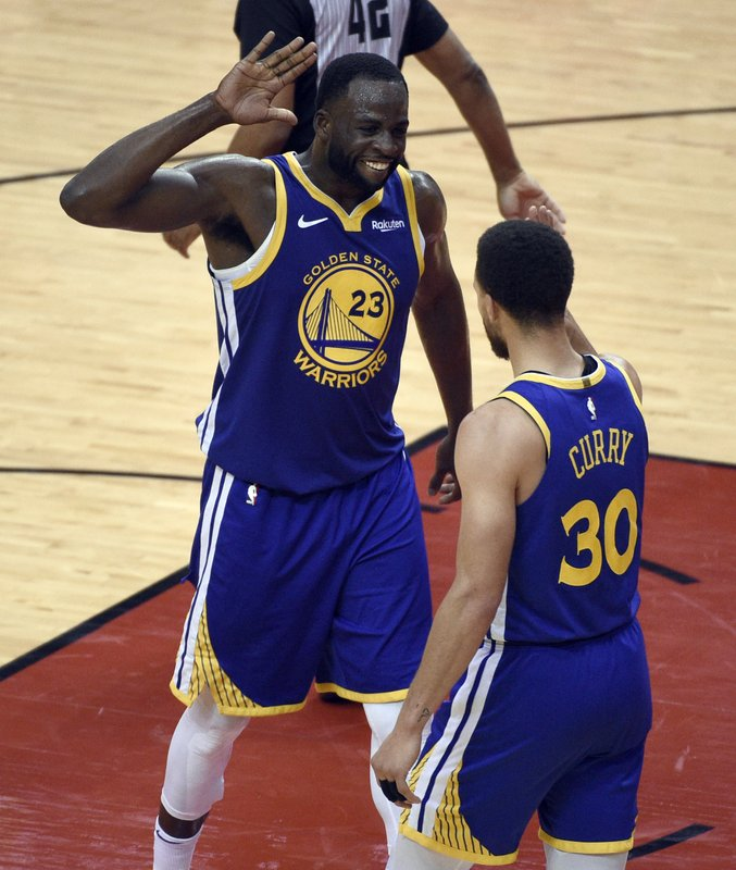 Golden State Warriors' Draymond Green (23) and Stephen Curry (30) celebrate in the closing seconds of Game 6 of the team's second-round NBA basketball playoff series against the Houston Rockets on Friday, May 10, 2019, in Houston. (AP Photo/Eric Christian Smith)