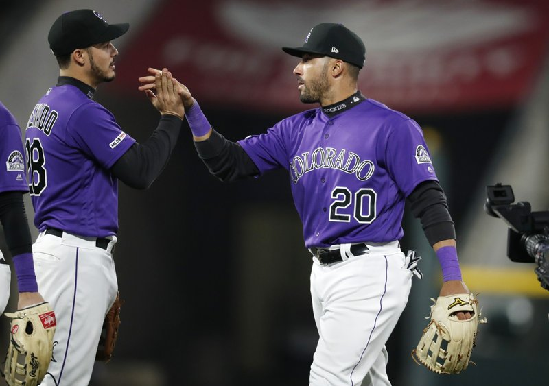 Colorado Rockies third baseman Nolan Arenado, left, center fielder Ian Desmond celebrate the team's win in a baseball game against the San Diego Padres Friday, May 10, 2019, in Denver. (AP Photo/David Zalubowski)