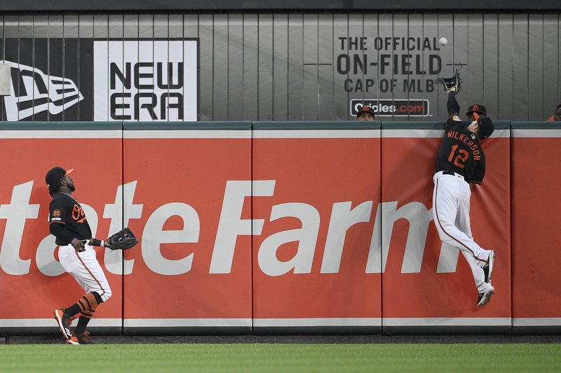 Baltimore Orioles center fielder Stevie Wilkerson (12) leaps in vain for a two-run home run by Los Angeles Angels' Mike Trout during the third inning of a baseball game Friday, May 10, 2019, in Baltimore. (AP Photo/Nick Wass)
