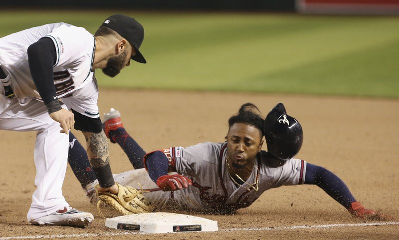 Atlanta Braves' Ozzie Albies, right, is tagged out by Arizona Diamondbacks first baseman Christian Walker, left, on a pickoff during the ninth inning of a baseball game Friday, May 10, 2019, in Phoenix. (AP Photo/Ross D. Franklin)