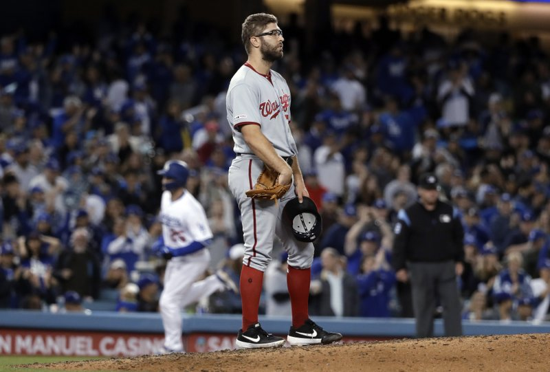 Washington Nationals relief pitcher Matt Grace, center, stands on the mound after giving up a two-run home run to Los Angeles Dodgers' David Freese, background, during the seventh inning of a baseball game Friday, May 10, 2019, in Los Angeles. (AP Photo/Marcio Jose Sanchez)