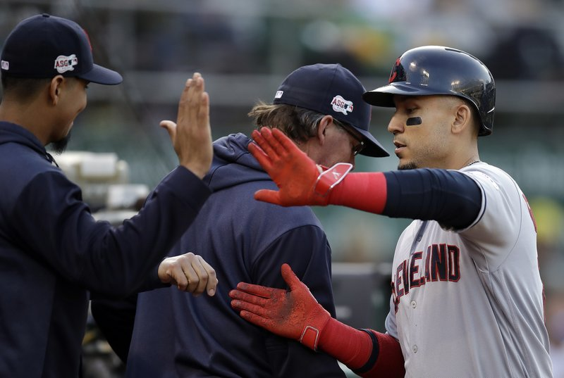 Cleveland Indians' Carlos Gonzalez, right, is congratulated after scoring against the Oakland Athletics during the second inning of a baseball game Friday, May 10, 2019, in Oakland, Calif. (AP Photo/Ben Margot)