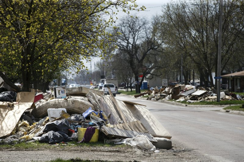 In this Tuesday, April 16, 2019 photo, residents belongings mix with flood damaged housing materials in piles along the side of the roads ready to be picked up and disposed in Hamburg, Iowa. (Brian Powers/The Des Moines Register via AP)
