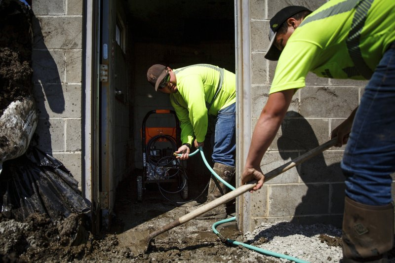 In this Wednesday, April 24, 2019 photo, Wyatt Burge, 21, left, of Hamburg, and Trey Varellas, 24 of Hamburg, work to clean out a pump station that had been swamped with flood water in Hamburg, Iowa. (Brian Powers/The Des Moines Register via AP)