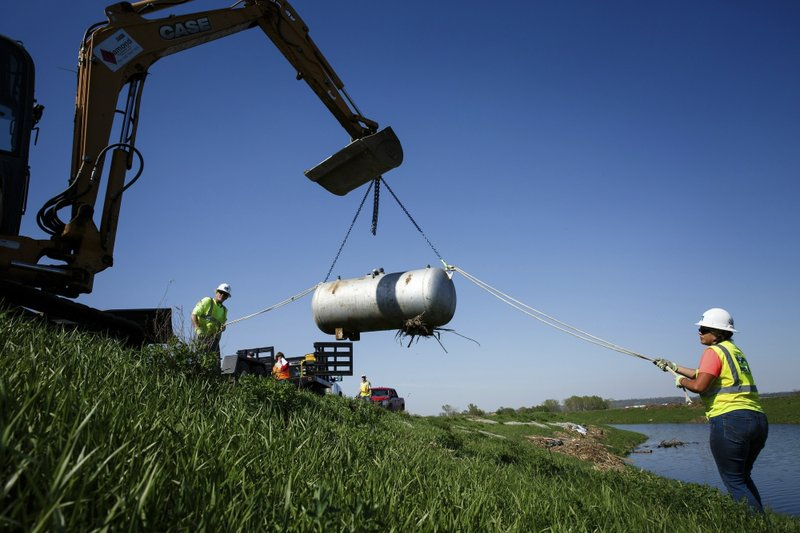 In this Wednesday, April 24, 2019 photo, Kamailelani Napoleon, with Environmental Restoration, works with Bruce Amsden to remove an orphaned LP tank from the side of levee on W, outside of Pacific Junction, Iowa. (Brian Powers/The Des Moines Register via AP)