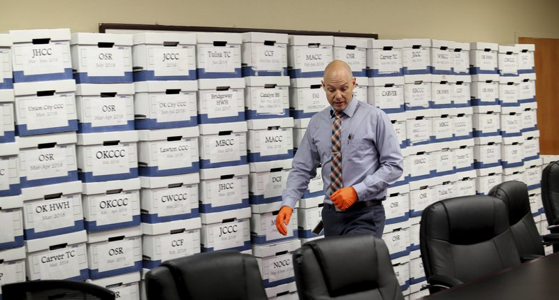 Oklahoma Department of Corrections spokesman Matt Elliott walks past boxes of cell phones that have been confiscated in Oklahoma prisons, in Oklahoma City, on Thursday, May 1, 2019. (Doug Hoke/The Oklahoman via AP)