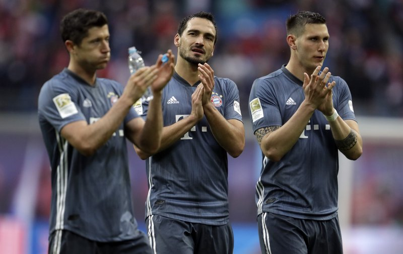 Bayern forward Robert Lewandowski, left, defender Mats Hummels, center and defender Niklas Suele greet supporters at the end of the German Bundesliga soccer match between Leipzig and Bayern Munich at the Red Bull Arena stadium in Leipzig, Germany, Saturday, May 11, 2019. (AP Photo/Michael Probst)