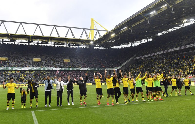 Dortmund players celebrate in front of the fans at the end of the German Bundesliga soccer match between Borussia Dortmund and Fortuna Duesseldorf in Dortmund, Germany, Saturday, May 11, 2019. (AP Photo/Martin Meissner)