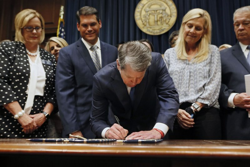 FILE - In this May 7, 2019, file photo, Georgia's Republican Gov. Brian Kemp, center, signs legislation in Atlanta, banning abortions once a fetal heartbeat can be detected, which can be as early as six weeks before many women know they're pregnant. (Bob Andres/Atlanta Journal-Constitution via AP, File)