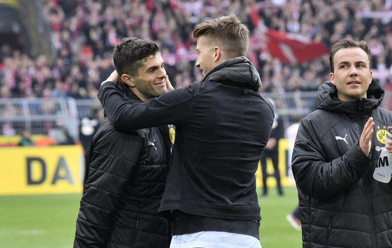 Dortmund's Marco Reus, center, talks to teammate Christian Pulisic, left, at the end of the German Bundesliga soccer match between Borussia Dortmund and Fortuna Duesseldorf in Dortmund, Germany, Saturday, May 11, 2019. (AP Photo/Martin Meissner)