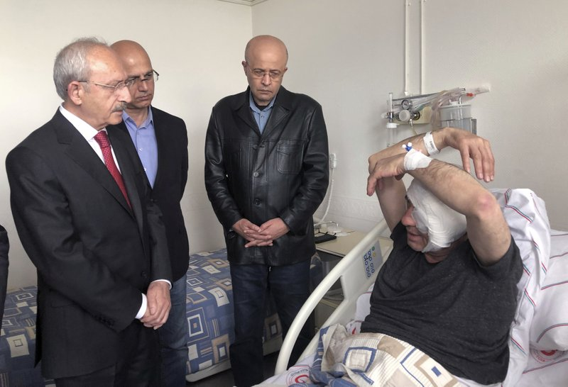 Yavuz Selim Demirag, a Turkish journalist critical of President Recep Tayyip Erdogan's government and its nationalist allies, speaks to visiting Kemal Kilicdaroglu, the leader of Turkey's main opposition Republican People's Party, left, as he rests in a hospital bed in Ankara, Turkey, Saturday, May 11, 2019. (AP Photo/Burhan Ozbilici)