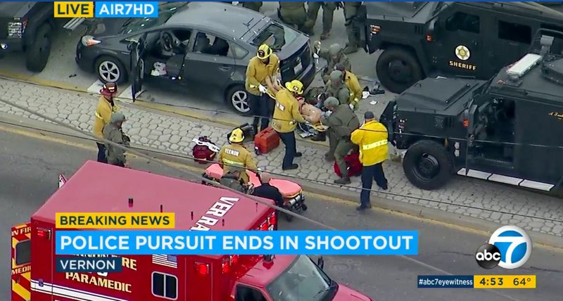 In this photo taken from video provided by KABC-TV, medics and officers tend to a wounded man after he was removed from his shot-up car, top left, at the conclusion of a wild car chase and rolling shootout in the Los Angeles area Friday afternoon, May 10, 2019. (KABC-TV via AP)