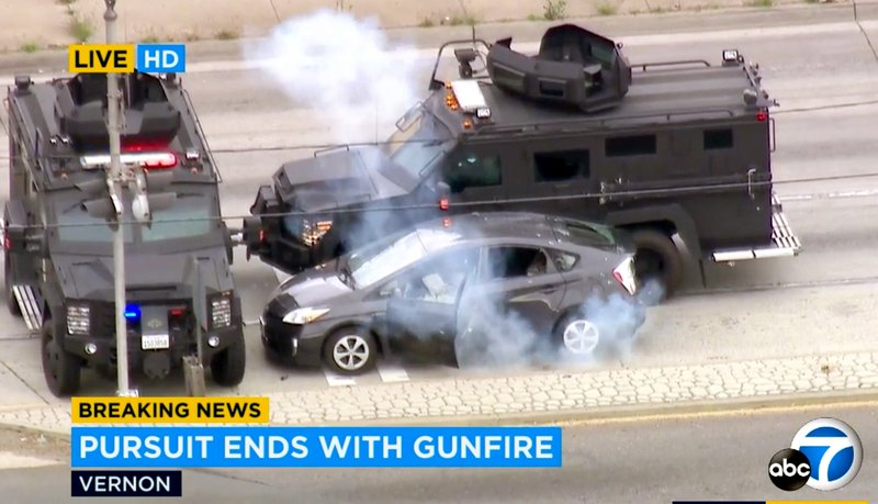 In this photo taken from video provided by KABC-TV, armored police vehicles block a car and deploy a flash bang device at the conclusion of a wild car chase and shootout in the Los Angeles area Friday afternoon, May 10, 2019. (KABC-TV via AP)
