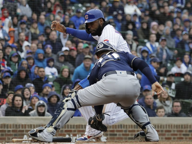 Milwaukee Brewers catcher Yasmani Grandal, right, tags out Chicago Cubs' Jason Heyward at home during the first inning of a baseball game Saturday, May 11, 2019, in Chicago. (AP Photo/Nam Y. Huh)