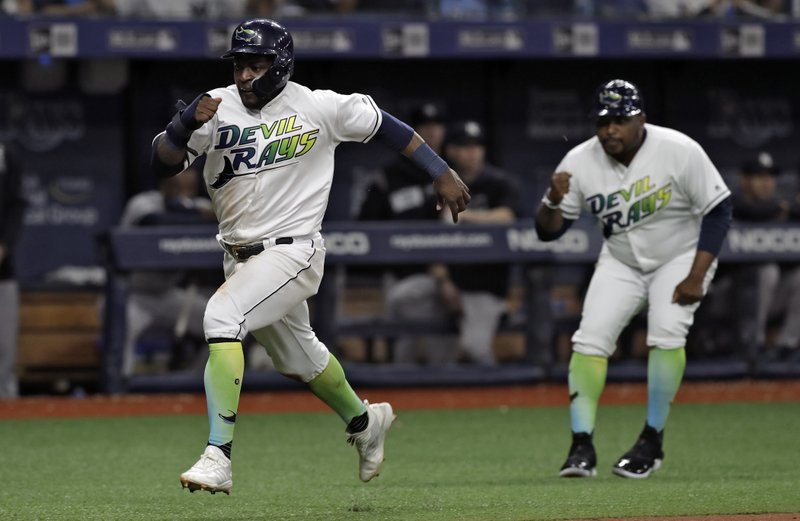Tampa Bay Rays' Guillermo Heredia, left, gets advice from third base coach Rodney Linares as he scores on a single by Ji-Man Choi during the sixth inning of a baseball game against the New York Yankees on Saturday, May 11, 2019, in St. (AP Photo/Chris O'Meara)