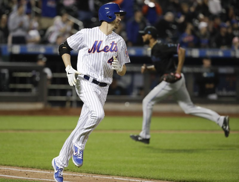 New York Mets' Jacob deGrom, left, runs to first base with an RBI single during the sixth inning of the team's baseball game against the Miami Marlins on Saturday, May 11, 2019, in New York. (AP Photo/Frank Franklin II)