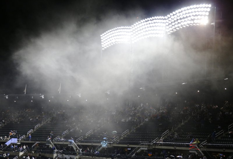 Fans watch the Miami Marlins play the New York Mets in the rain during the eighth inning of a baseball game Saturday, May 11, 2019, in New York. (AP Photo/Frank Franklin II)