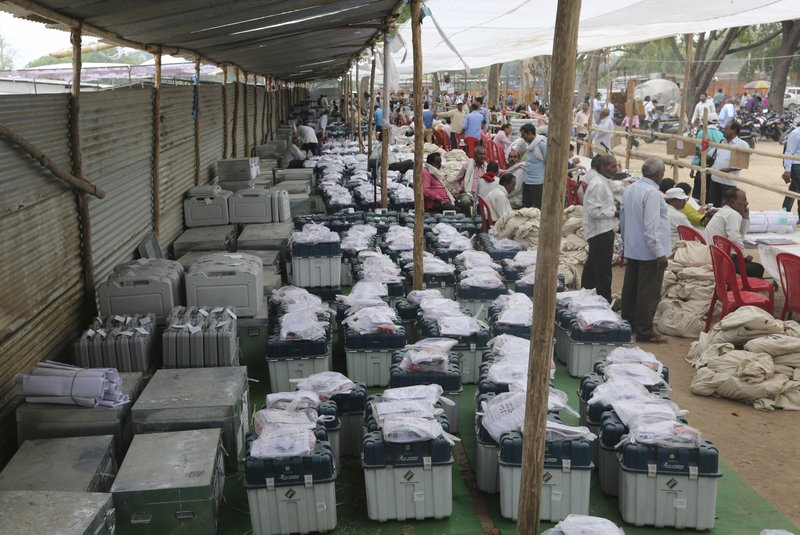 Election officers gather at a distribution center to receive electronic voting machines for their respective polling stations  on the eve of polling in Prayagraj, India, Saturday, May 11, 2019. (AP Photo/Rajesh Kumar Singh)