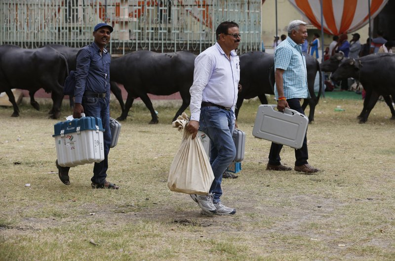 Election officers carry electronic voting machines before proceeding towards their allotted polling stations on the eve of polling in Prayagraj, India, Saturday, May 11, 2019. (AP Photo/Rajesh Kumar Singh)