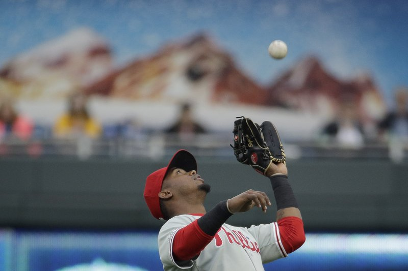 Philadelphia Phillies shortstop Jean Segura catches a fly ball for an out against Kansas City Royals' Whit Merrifield during the first inning of a baseball game Saturday, May 11, 2019, in Kansas City, Mo. (AP Photo/Charlie Riedel)