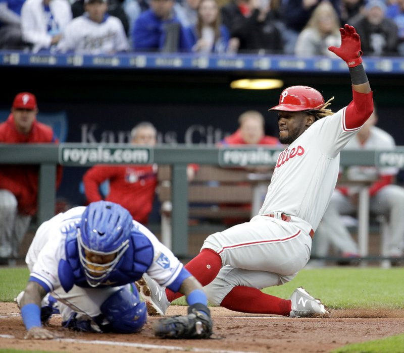 Philadelphia Phillies' Odubel Herrera, right, beats the tag at home by Kansas City Royals catcher Martin Maldonado to score on a ground-out hit by Andrew McCutchen during the fourth inning of a baseball game Saturday, May 11, 2019, in Kansas City, Mo. (AP Photo/Charlie Riedel)