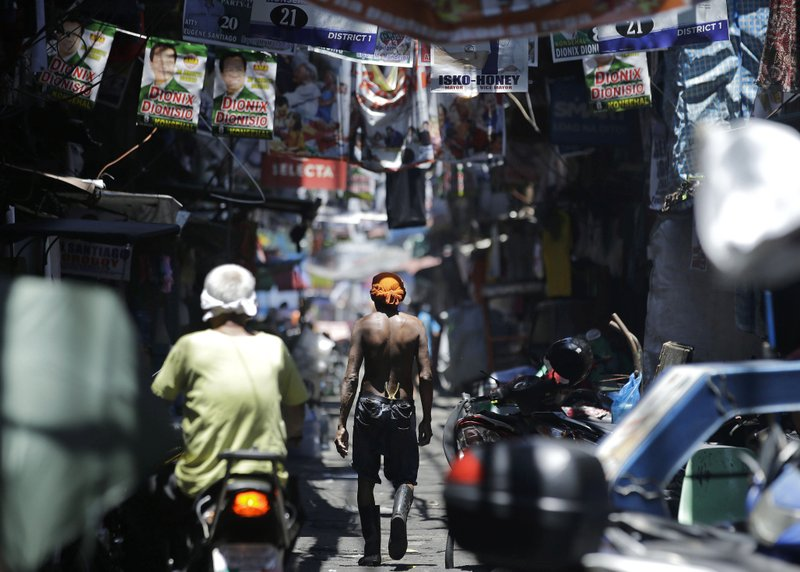 In this Thursday, May 9, 2019, photo, a man walks past election banners in the slum district of Tondo, Manila, Philippines. (AP Photo/Aaron Favila)