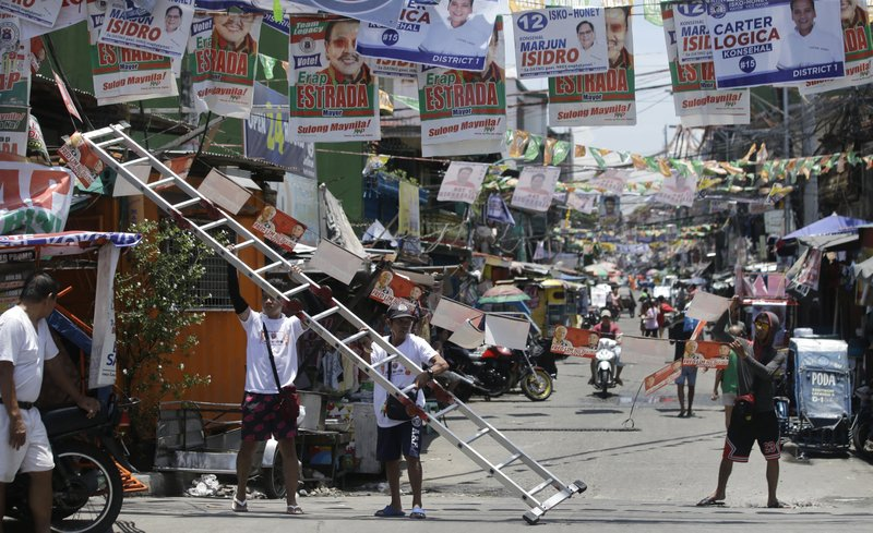In this Thursday, May 9, 2019, photo, workers place election campaign posters along a street at the slum district of Tondo, Manila, Philippines. (AP Photo/Aaron Favila)