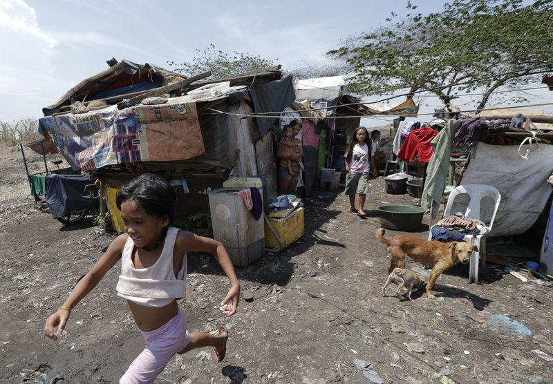 In this Thursday, May 9, 2019, photo, children play outside their shanty at Manila's former dumpsite Smokey Mountain, Philippines. (AP Photo/Aaron Favila)
