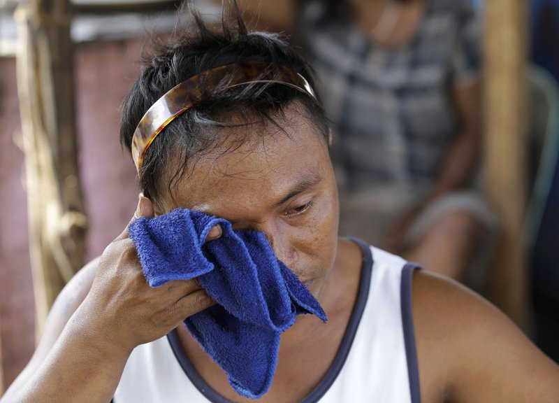 In this Thursday, May 9, 2019 photo, Arturo Veles wipes a tear as he talks to The Associated Press outside his family's shanty at Manila's former dumpsite Smokey Mountain, Philippines. (AP Photo/Aaron Favila)