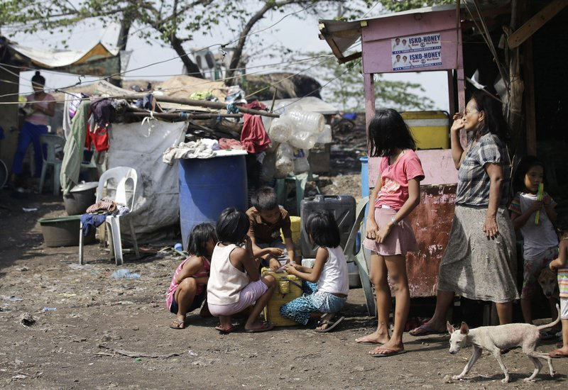 In this Thursday, May 9, 2019 photo, Agnes Veles, right, watches as children count their day's earning from selling ice candy outside their shanty at Manila's former dumpsite Smokey Mountain, Philippines. (AP Photo/Aaron Favila)