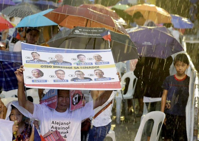 In this Wednesday, May 8, 2019, photo, supporters brave the rain during the last campaign rally together by the opposition senatorial candidates in suburban Quezon city, northeast of Manila, Philippines. (AP Photo/Bullit Marquez)