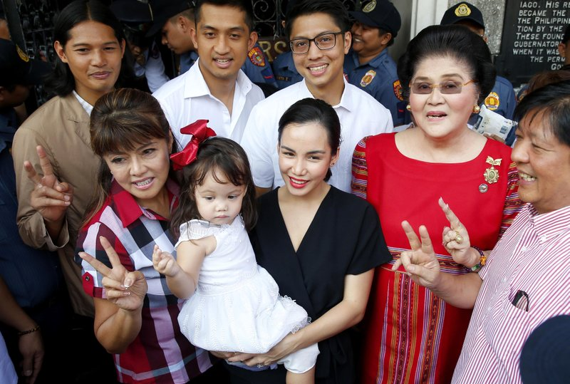 In this photo Oct. 16, 2018, photo, Imee Marcos, left front, the eldest daughter of ousted Philippine dictator Ferdinand Marcos, poses with her family, including her mother and former First Lady Imelda Marcos, second from right, and brother Ferdinand